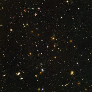 """Galaxies, galaxies everywhere - as far as the NASA/ESA Hubble Space Telescope can see. This view of nearly 10,000 galaxies is the deepest visible-light image of the cosmos. Called the Hubble Ultra Deep Field, this galaxy-studded view represents a """"deep"""" core sample of the universe, cutting across billions of light-years. The snapshot includes galaxies of various ages, sizes, shapes, and colours. The smallest, reddest galaxies, about 100, may be among the most distant known, existing when the universe was just 800 million years old. The nearest galaxies - the larger, brighter, well-defined spirals and ellipticals - thrived about 1 billion years ago, when the cosmos was 13 billion years old. In vibrant contrast to the rich harvest of classic spiral and elliptical galaxies, there is a zoo of oddball galaxies littering the field. Some look like toothpicks; others like links on a bracelet. A few appear to be interacting. These oddball galaxies chronicle a period when the universe was younger and more chaotic. Order and structure were just beginning to emerge. The Ultra Deep Field observations, taken by the Advanced Camera for Surveys, represent a narrow, deep view of the cosmos. Peering into the Ultra Deep Field is like looking through a 2.5 metre-long soda straw. In ground-based photographs, the patch of sky in which the galaxies reside (just one-tenth the diameter of the full Moon) is largely empty. Located in the constellation Fornax, the region is so empty that only a handful of stars within the Milky Way galaxy can be seen in the image. In this image, blue and green correspond to colours that can be seen by the human eye, such as hot, young, blue stars and the glow of Sun-like stars in the disks of galaxies. Red represents near-infrared light, which is invisible to the human eye, such as the red glow of dust-enshrouded galaxies. The image required 800 exposures taken over the course of 400 Hubble orbits around Earth. The total amount of exposure time was 11.3 days,"""